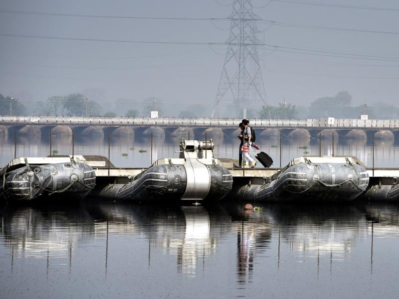 Two women walk on a pontoon bridge on the ecologically-sensitive Yamuna floodplains. (Sushil Kumar/ht photo)