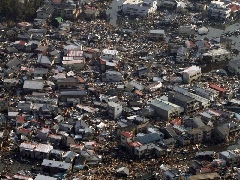 Collapsed houses and debris in a field in Kesennuma, Miyagi prefecture on March 12, 2011. (AFP File Photo)