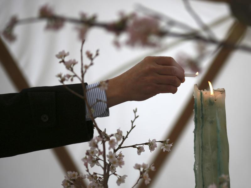 A man lights a candle to mourn for victims of the 2011 earthquake and tsunami before a memorial event in Tokyo. (AP Photo)