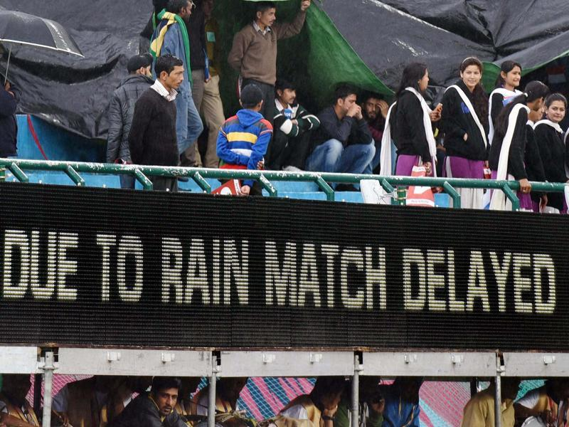 Spectators try to protect themselves under a structure and plastic sheets the T20 World Cup match between Oman and Netherlands was delayed. (PTI Photo)