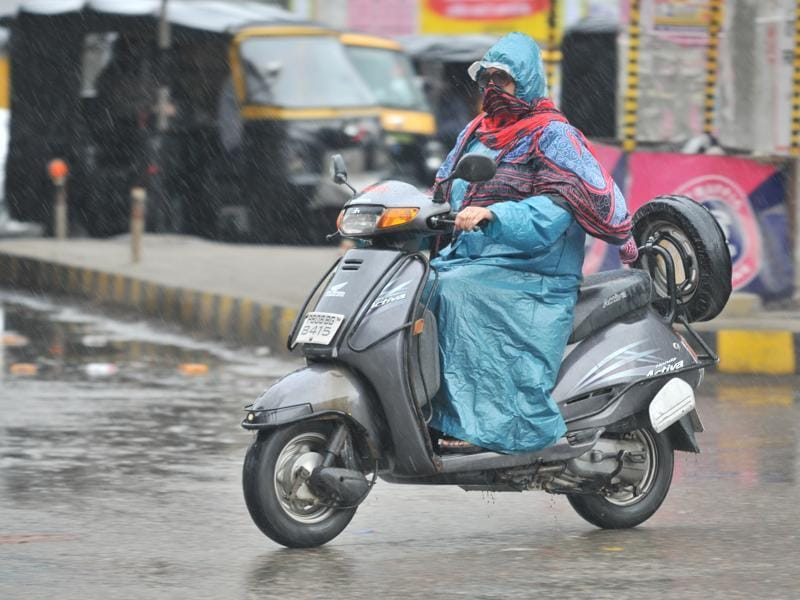 A woman rides through rain in Jalandhar. (Pardeep Pandit/ht)