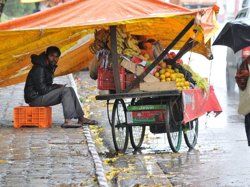 A roadside vendor protects  himself and his products under  a plastic sheet as it rains  in Jammu.   (Nitin Kanotra/HT )