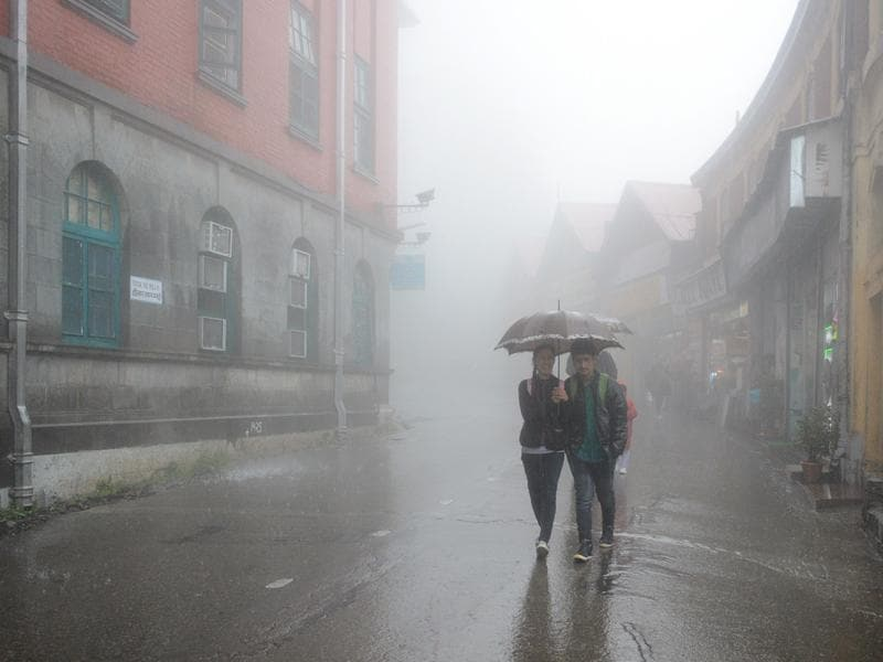Students walk through rain and fog at Mall Road, Shimla, on Saturday. (Deepak sansta/HT)