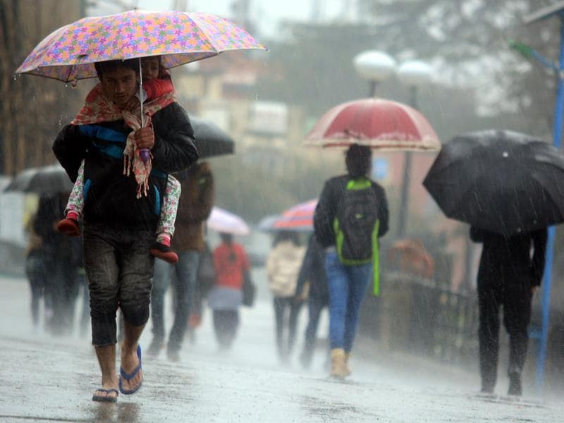 A boy carries his sister during heavy rain at the Ridge in Shimla on Saturday. (deepak sansta/HT)