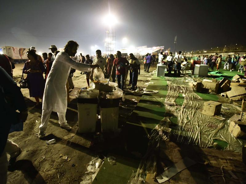 People throw garbage in the over flooded bins after the end of 3 day World Cultural Festival on the banks of Yamuna. (Arun Sharma/Hindustan Times)