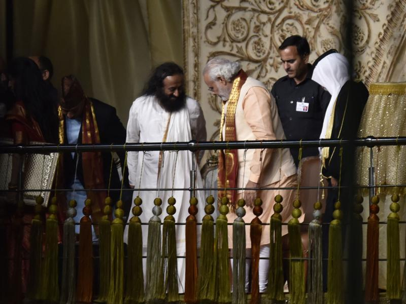 Prime Minister Narendra Modi and Sri Sri Ravi Shankar share a few words before the PM addresses the crowd at the WCF. (Virendra Singh Gosain/HT Photo)