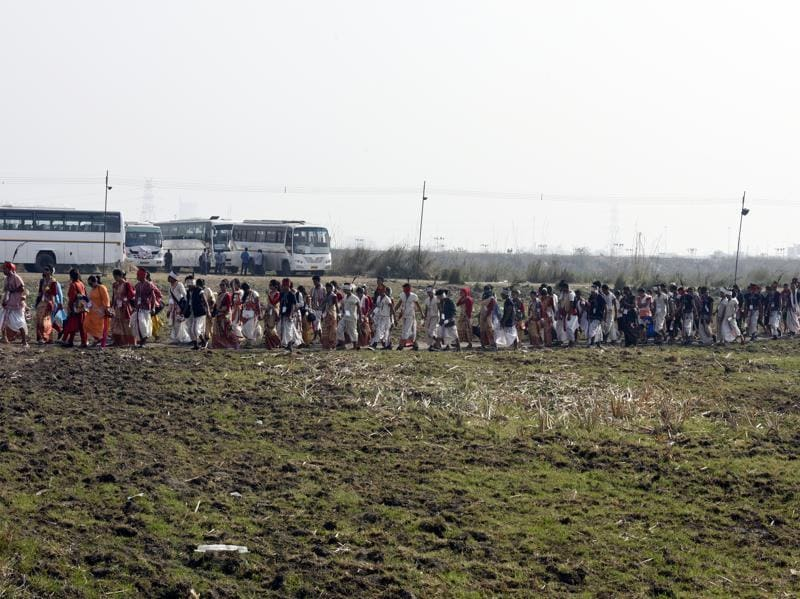 People walk on Yamuna floodplains to reach the World Culture Festival venue. Showers and dust storm lashed the expansive area making it difficult for people to walk and vehicles to negotiate the muddy terrain. (Sonu Mehta/HT Photo)