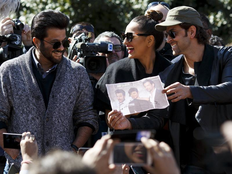 Anil Kapoor, Sonakshi Sinha and Hrithik Roshan look at a photograph which a fan asked them to autograph as they take part in a flashmob in Madrid. (REUTES)