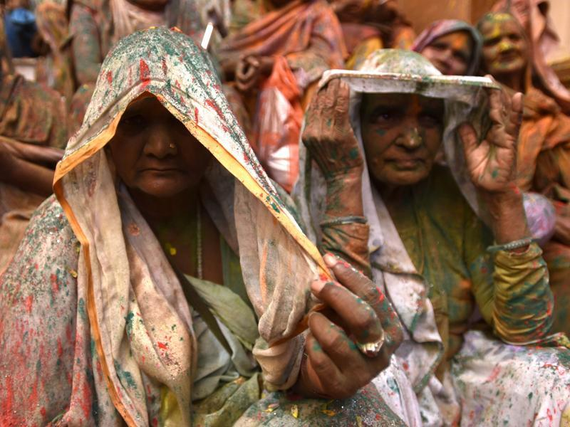 Widows rest after participating in Holi celebrations. In many parts of India widows are barred from celebrating the festival but women at the shelter for widows broke the bygone norm and enjoyed the festival. (Ajay Aggarwal/HT Photo)