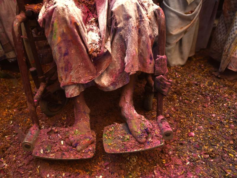 An old woman sits on her chair amid Holi celebrations.It is for the first time Holi celebration was organised at an ancient Gopinath Temple of Lord Krishna in which around a thousand widows from Vrindavan and Varanasi splashed colour at each other. (Ajay Aggarwal/HT Photo)