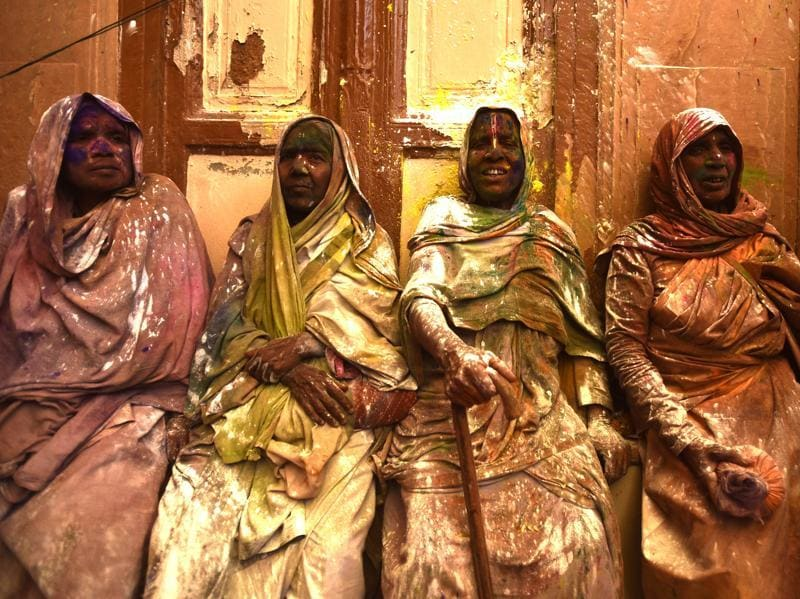 Widows smeared in Gulal rest after taking part in Holi celebrations organized by non-governmental organization, Sulabh International at Gopinath temple at Vrindavan. In many parts of India widows are barred from celebrating the festival but women at the shelter for widows broke the bygone norm and enjoyed the festival. (Ajay Aggarwal/HT Photo)