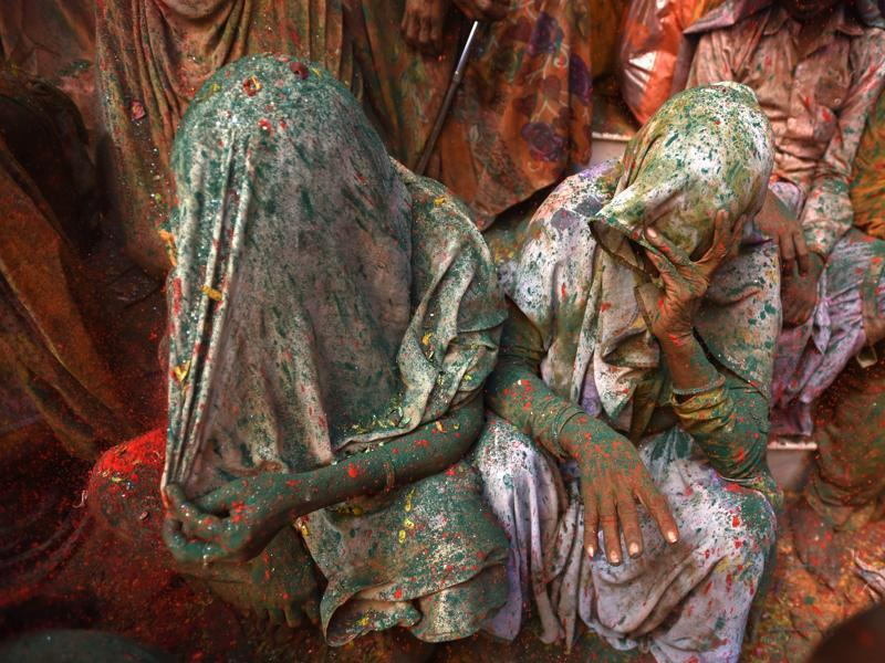 Widows smeared in Gulal rest after taking part in Holi celebrations at Vrindavan. It is for the first time Holi celebration was organised at an ancient Gopinath Temple of Lord Krishna in which around a thousand widows from Vrindavan and Varanasi splashed colour at each other. (Ajay Aggarwal/HT Photo)
