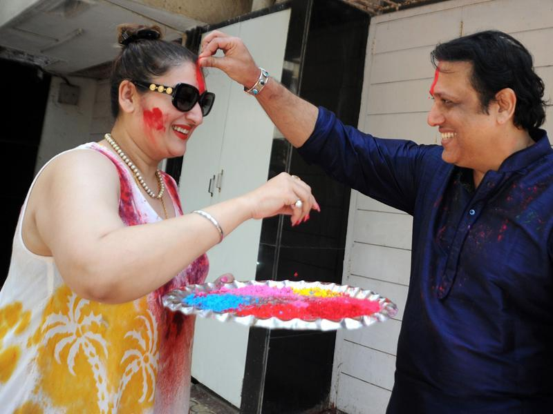 Govinda places colour on the forehead of his wife Sunita Ahuja during their Holi celebration. (AFP)
