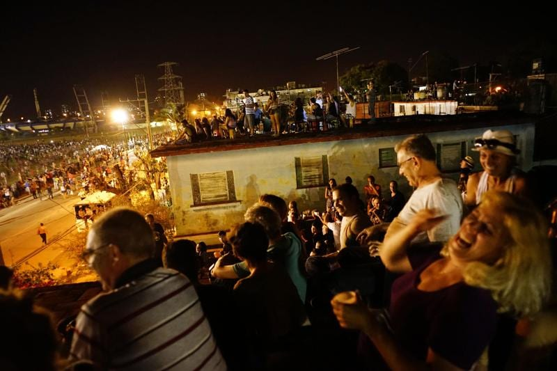 People watch the Rolling Stones concert on the terraces of the houses near the venue in Havana, Cuba, Friday March 25, 2016.  (AP Photo)