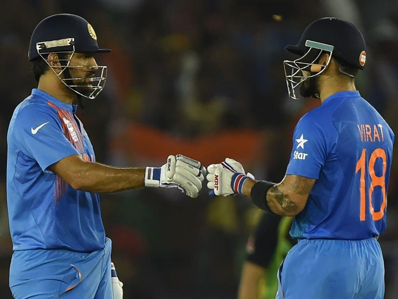 Kohli (R) exchanges a fist pump with captain Mahendra Singh Dhoni. With 39 required off the last 3 overs, the duo hit 39 in 13 balls, with 7 fours and one six to overhaul the target.   (AFP)