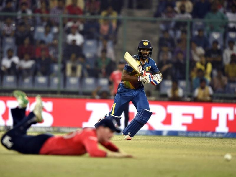 Chamara Kapugedera watches his shot as an England fielder dives in an attempt to stop it. (Sanjeev Verma/HT Photo)