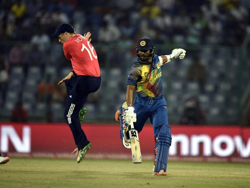 England`s Eoin Morgan jumps to avoid getting hit by the ball as Dinesh Chandimal makes his ground. (Sanjeev Verma/HT Photo)