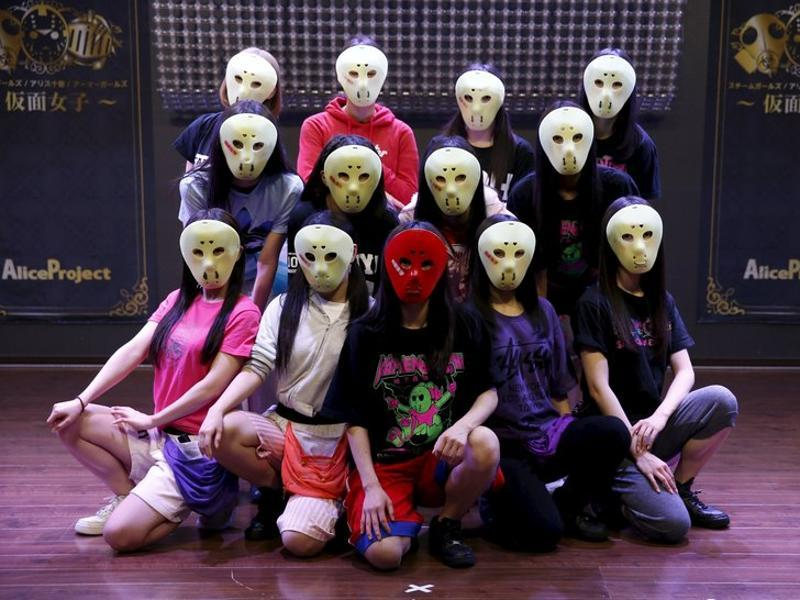 Members of Japanese idol group Kamen Joshi (Masked Girls) pose for a photo after a rehearsal for a concert at their theatre in Tokyo's Akihabara district. (REUTERS)