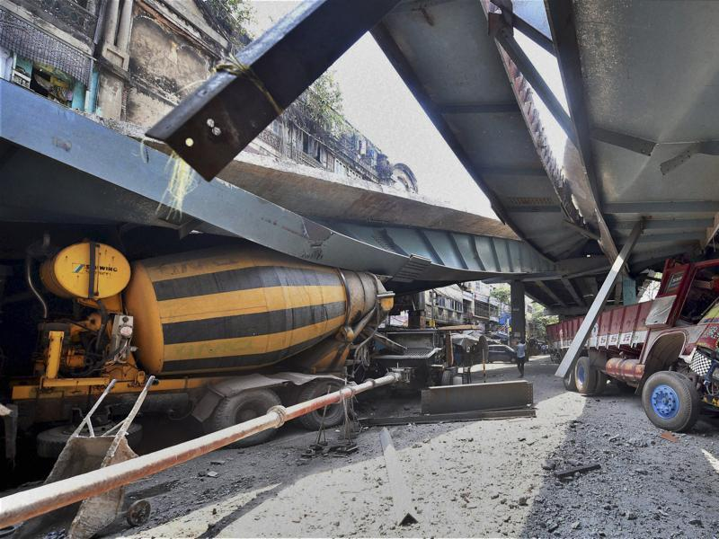 Vehicles are seen trapped under a partially collapsed overpass in Kolkata. (PTI via AP Photo)