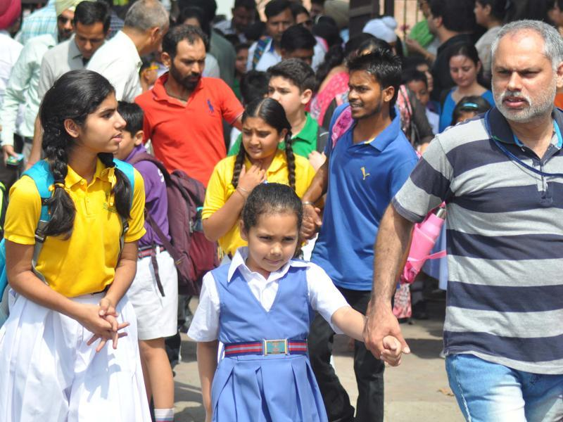 Students come out as parents come to pick them up, after the first day of school in the new session in Chandigarh on Monday. (karun sharma/HT photo)