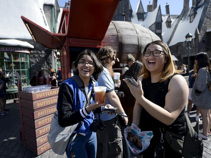 Guests try out Butterbeer served from a large barrel shaped Butterbeer cart in Hogsmeade Village during a soft opening and media tour of The Wizarding World of Harry Potter theme park at the Universal Studios Hollywood in Los Angeles. (REUTERS)