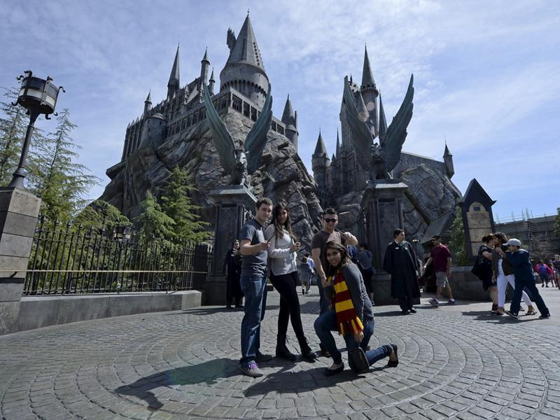 Guests pose before they enter Hogwarts School during a soft opening and media tour of The Wizarding World of Harry Potter theme park at the Universal Studios Hollywood in Los Angeles. (REUTERS)