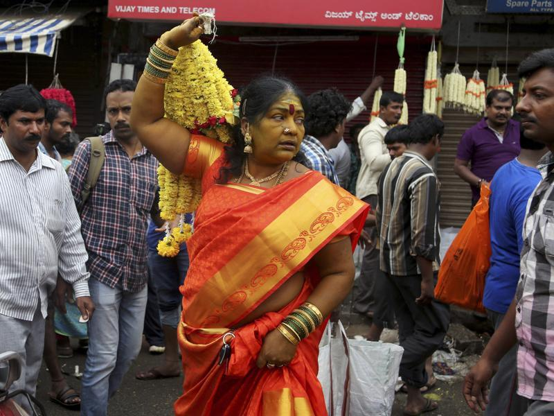 Woman in traditional attire carries a bunch of flowers after shopping at a wholesale market on the occasion of Ugadi in Bangalore.  (AP)