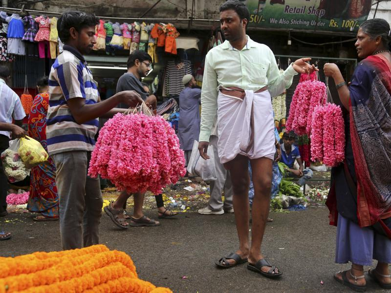 A shopper bargains with flower vendors at a wholesale market on the occasion of Ugadi in Bangalore. (AP)