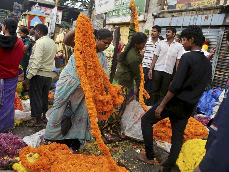 Flower vendors arrange flowers at a wholesale market on the occasion of Ugadi in Bangalore. (AP)