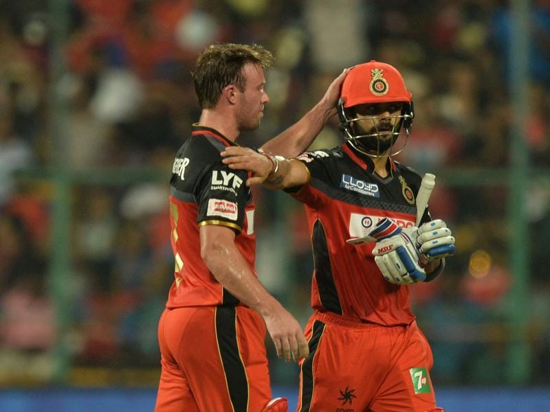 Virat Kohli (R) and AB De Villiers congratulate each other as Kohli walks back to the pavilion after being dismissed for 75 runs. (AFP)