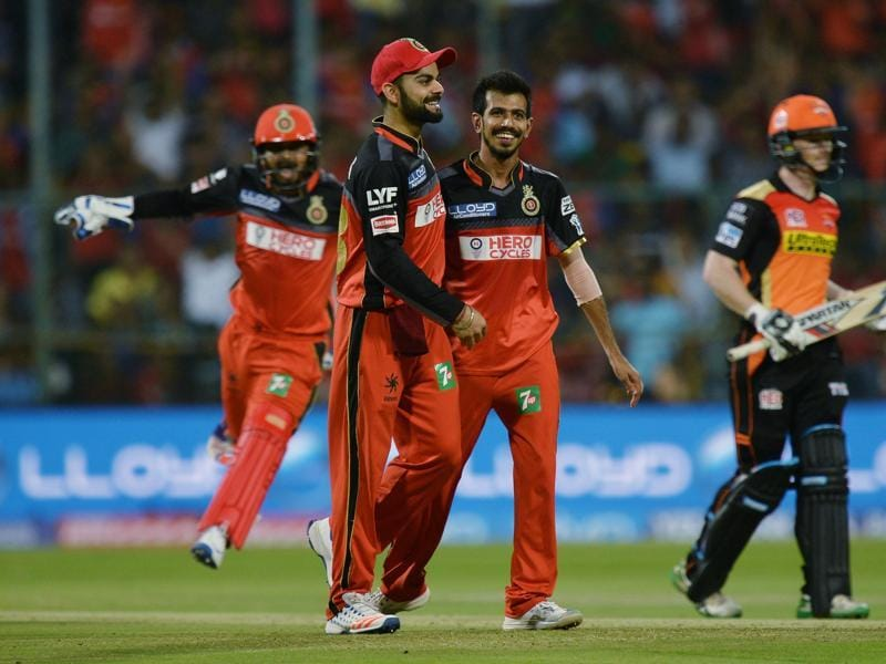 Yuzvendra Chahal (C) celebrates the wicket of Sunrisers Hyderabad Deepak Hooda (unseen) with his team captain Virat Kohli (2L), during the 2016 Indian Premier League (IPL) match between Royal Challengers Bangalore and Sunrisers Hyderabad at The M Chinnaswamy Stadium in Bangalore on April 12, 2016. (AFP)