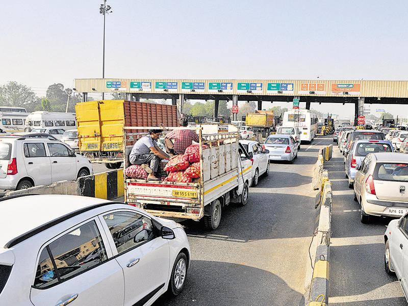In the absence of separate lanes for commercial and private vehicles, commuters are forced to wait at the toll plaza in long queues. (Abhinav Saha/HT Photo)