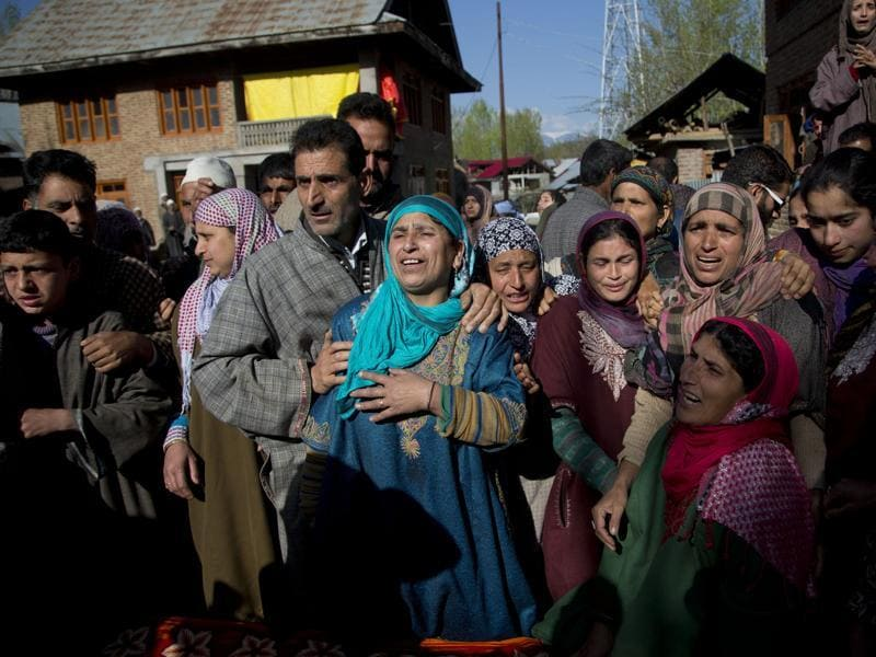 Relatives of Raja Begum wail as her body arrives at her residence in Langate.  (AP)