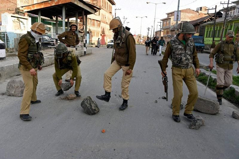 Policemen remove the barricades put up by angry protesters during clashes in Downtown Srinagar on Tuesday. Fresh clashes were reported between residents and the army as the area remained tense. (PTI)