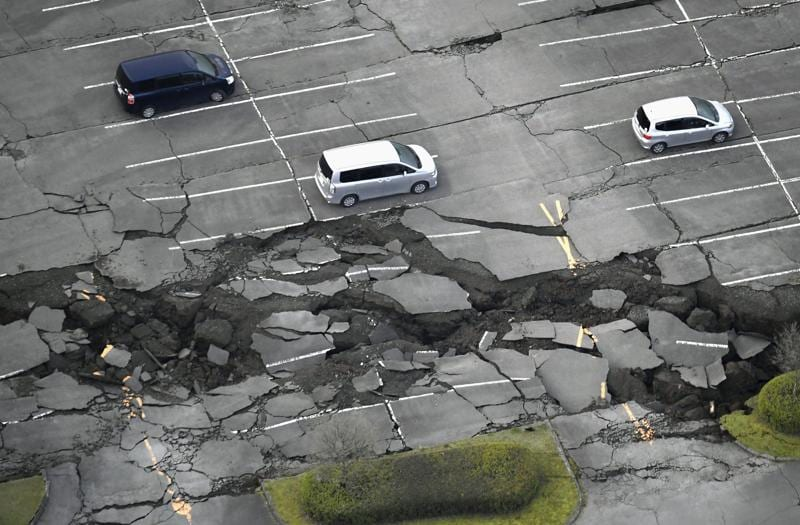 Vehicles sit at a parking lot damaged by an earthquake at Minamiaso in Kumamoto prefecture. (AP)