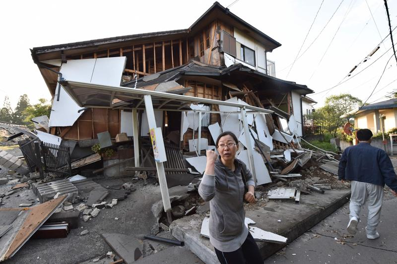 A couple heads to their home past a collapsed house in Mashiki. (AFP)