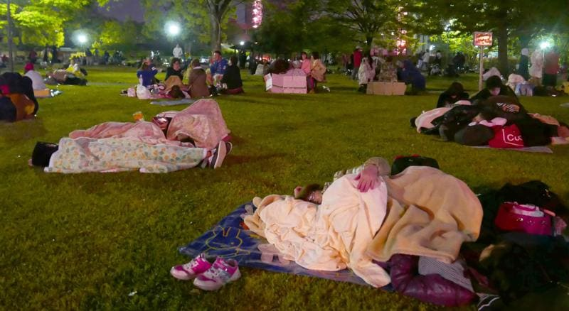 People rest on grass in fear of aftershock at an evacuation site in Kumamoto. (AP)