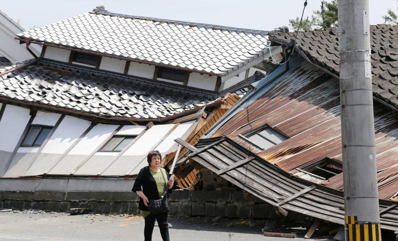 A woman walks past houses destroyed by Thursday's earthquake in Mashiki, Kumamoto prefecture, southern Japan, Friday, April 15, 2016.  (AP)