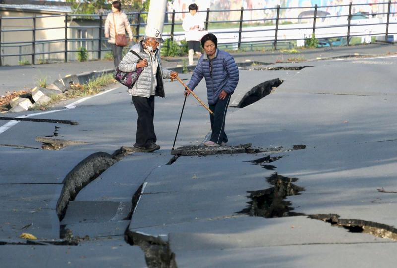 Local residents look at cracks caused by an earthquake on a road in Mashiki town. (REUTERS)