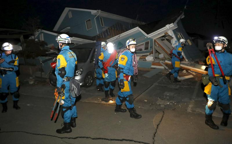 Police officers check a collapsed house after an earthquake in Mashiki town. (REUTERS)