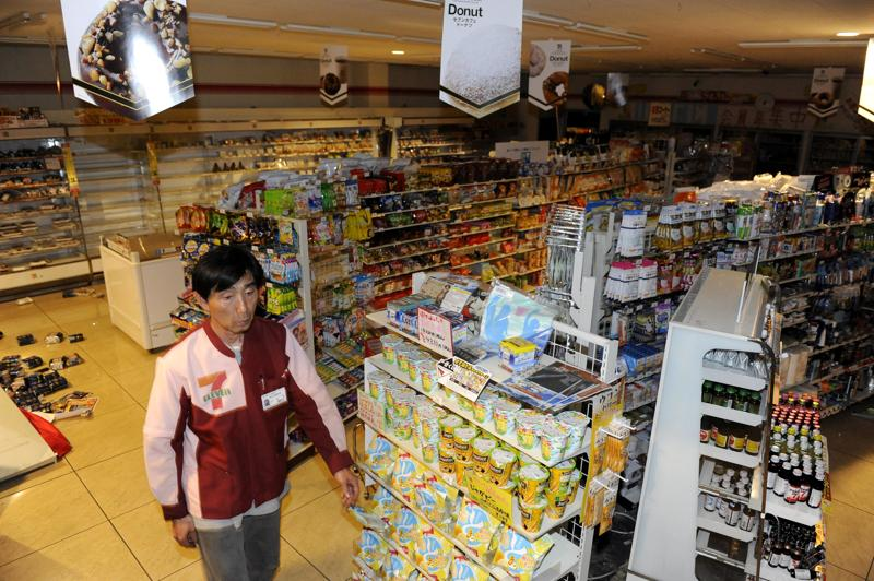 A worker surveys the damage at a 7 Eleven convenient store following an earthquake, Saturday, April 16, 2016, in Kumamoto, southern Japan.  (AP)