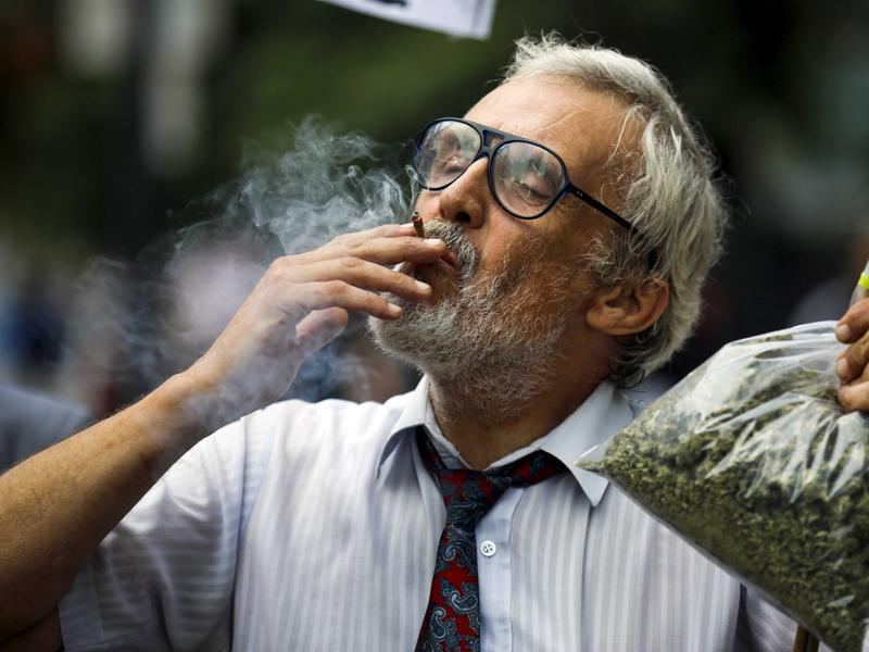 Activist Ray Turmel holds a bag of medical marijuana while he smokes a joint in Toronto. 420 has been increasingly used to protest for legalising weed. (REUTERS)
