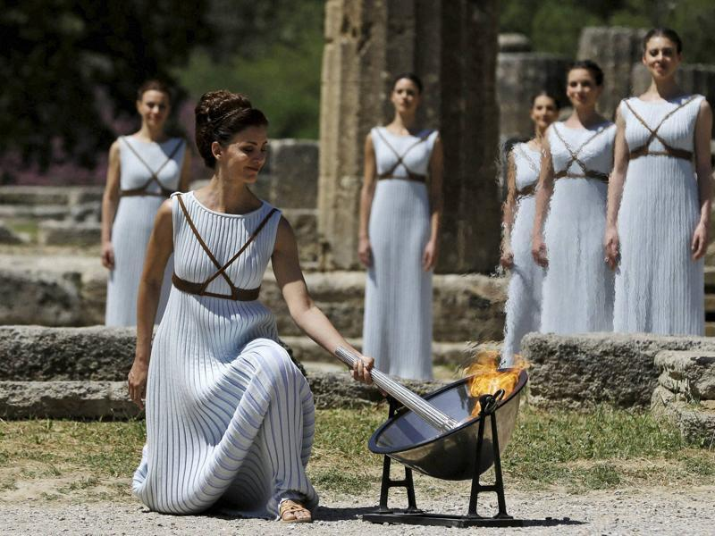 A dancer dressed as priestesses lights the Olympic flame with a parabolic mirror during the ceremonial lighting of the Olympic flame in Ancient Olympia, Greece. (AP Photo)