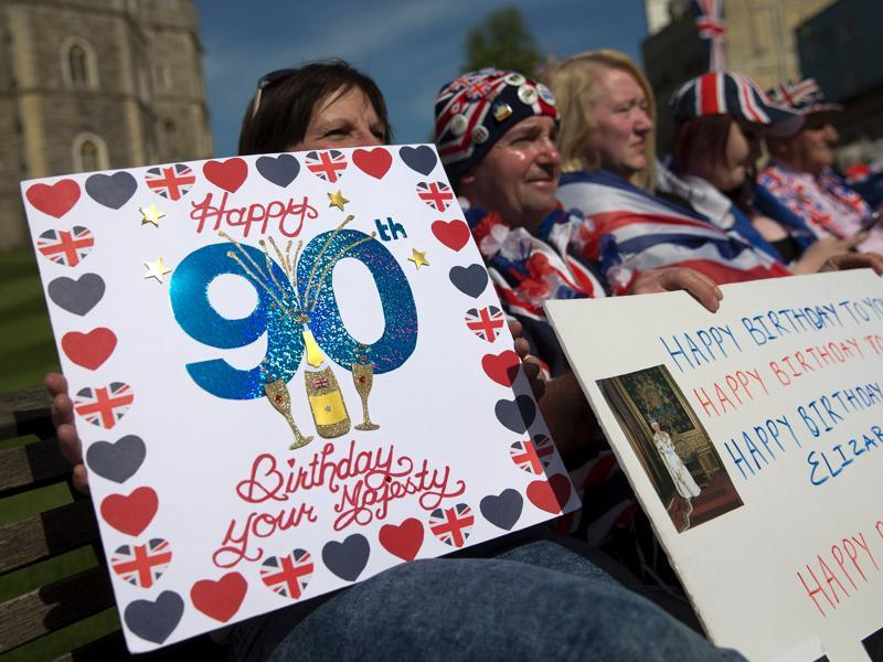Royal well-wishers hold placards wishing Britain's Queen Elizabeth II a happy 90th birthday as they wait in hope of seeing her following her engagements in Windsor, west of London. (AFP Photo)