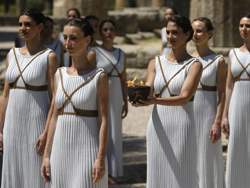 Dancers dressed as priestesses hold the Olympic flame during the ceremonial lighting of the Olympic flame in Ancient Olympia, Greece. (AP Photo)