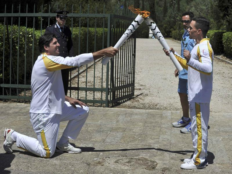 Olympic flame first torch bearer, Greek gymnast Eleftherios Petrounias (R) passes the torch to second bearer, former volleyball player Giovane Gavio from Brazil. (REUTERS Photo)