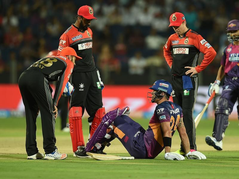 Rising Pune Supergiants batsman Kevin Pietersen sits on a ground after getting injured while batting as Royal Challengers Bangalore player AB de Villiers (2nd R) and captain Virat Kohli (L) speak during the 2016 Indian Premier League (IPL). (AFP Photo)