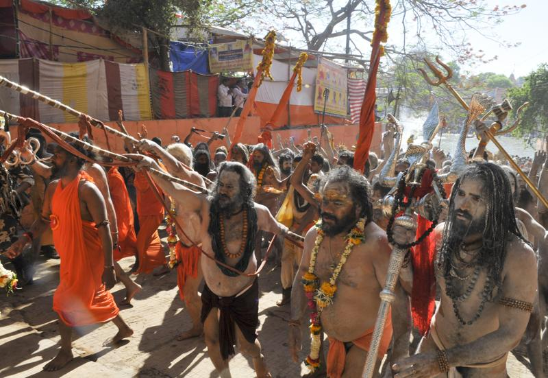 Before taking the plunge, processions of sadhus paraded through the town, brandishing their traditional swords and tridents, dancing and chanting mantras.  (Shankar Mourya/ Hindustan Times)