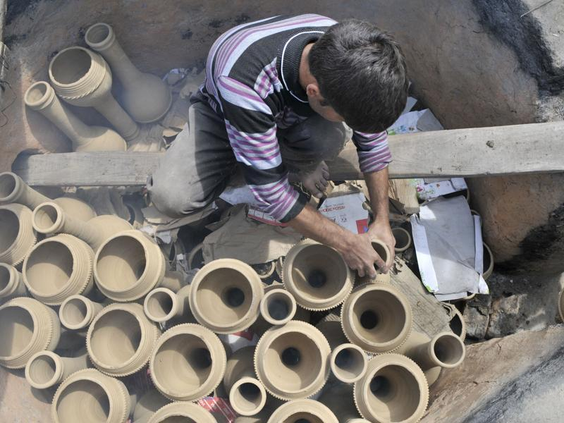 A potter arranging  set of Tumbaknaris for baking in a furnace.   (Waseem Andrabi/ HT)