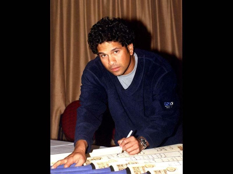 Sachin signs cricket bats for fans. The status he enjoys in India is literally godlike. Getty Images.